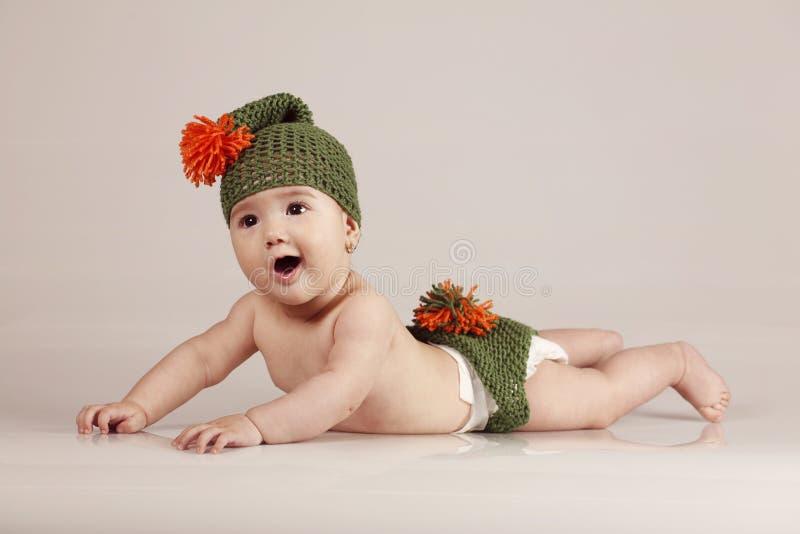 Pequeño babygirl lindo que se divierte y que sonríe en fondo aislado imagen de archivo libre de regalías