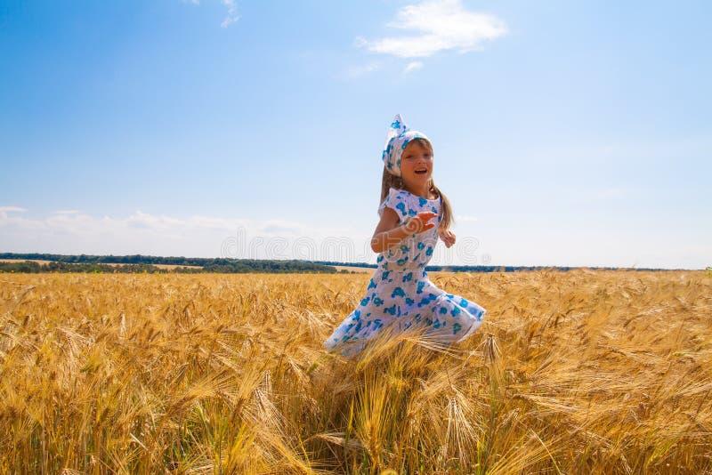 Pequeño baile feliz de la muchacha en un campo imágenes de archivo libres de regalías