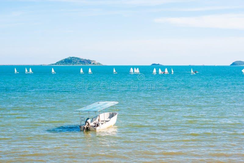 Pequeño barco de motor en el mar azul con la navegación en fondo imagen de archivo libre de regalías