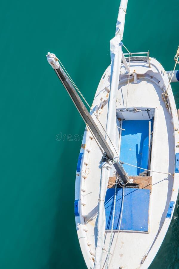 Pequeño barco de navegación blanco y azul vacío hermoso con el palo alto amarrado en el puerto Mar vivo de la turquesa Visión sup imagen de archivo