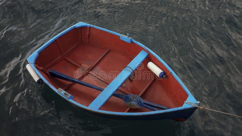 Pequeño barco de pesca de madera con un solo remo azul dentro, implicado cerca de un embarcadero contra el agua oscura, vergonzos foto de archivo libre de regalías