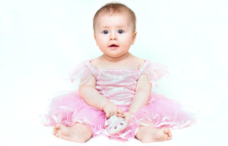 Pequeño bebé adorable en el vestido rosado que juega con su zapato rosado fotografía de archivo