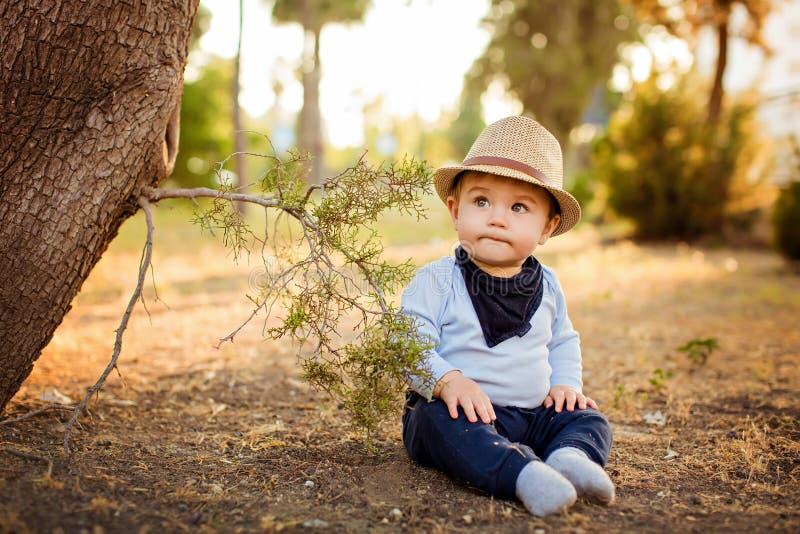 Pequeño bebé adorable en un sombrero de paja y pantalones azules que sientan w imagen de archivo