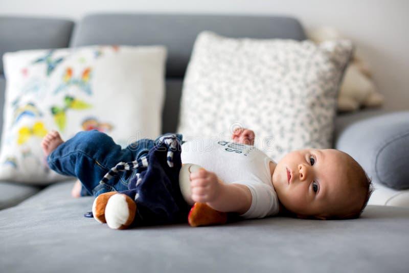 Pequeño bebé adorable, jugando con el juguete, mirando curiosamente imagenes de archivo
