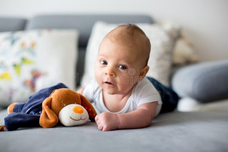 Pequeño bebé adorable, jugando con el juguete, mirando curiosamente foto de archivo libre de regalías