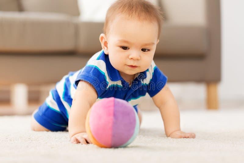 Pequeño bebé asiático dulce que juega con la bola del juguete imagenes de archivo