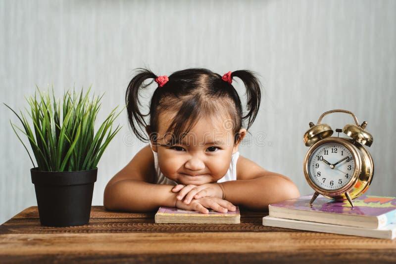 Pequeño bebé asiático lindo que hace la cara divertida o que sonríe mientras que libros de lectura con el despertador fotografía de archivo