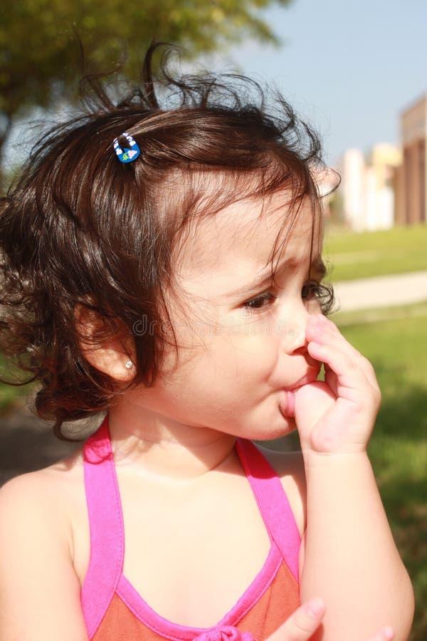 Pequeño bebé, aspirando su pulgar en el parque fotos de archivo