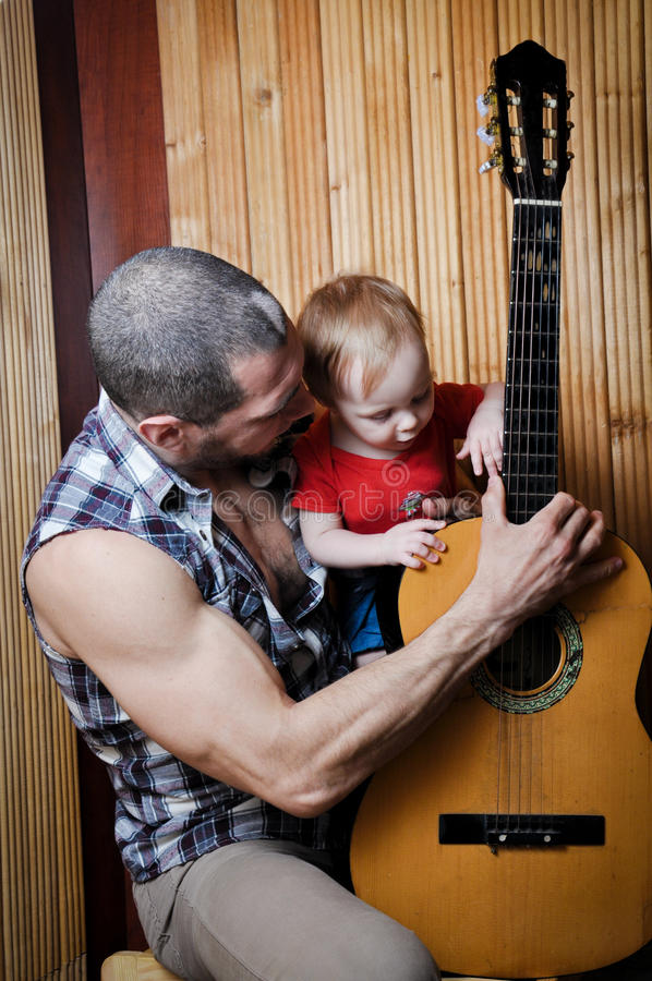 Pequeño bebé con su padre del inconformista que toca la guitarra en fondo de madera Foto vertical foto de archivo
