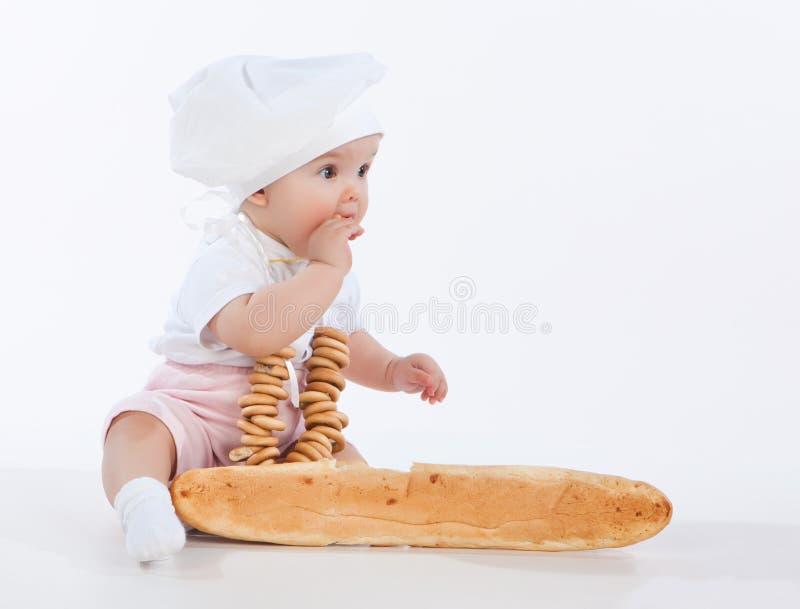Pequeño bebé del panadero con un pan largo y los panecillos. fotos de archivo libres de regalías