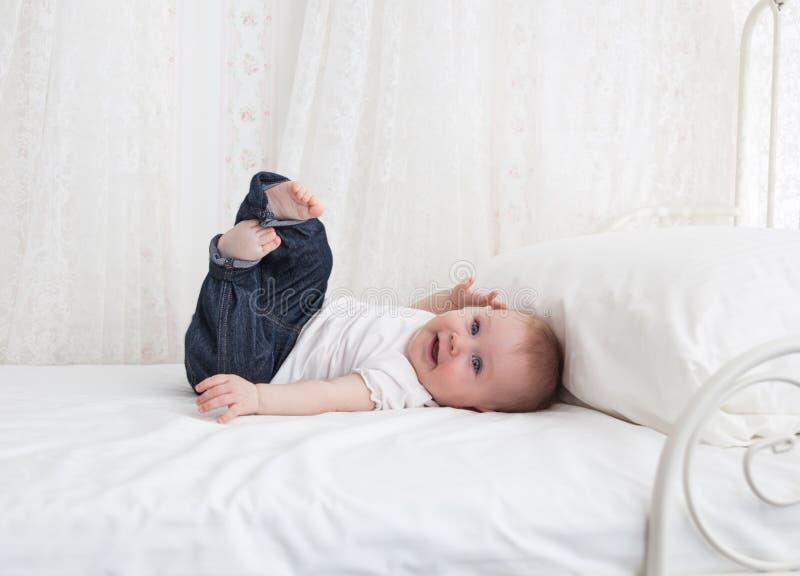 Pequeño bebé divertido en la cama blanca fotos de archivo libres de regalías