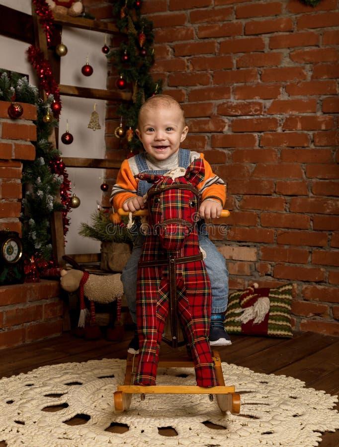 Pequeño bebé en el caballo mecedora, vestido en suéter y vaqueros Decoraciones de la Navidad o del Año Nuevo imagenes de archivo