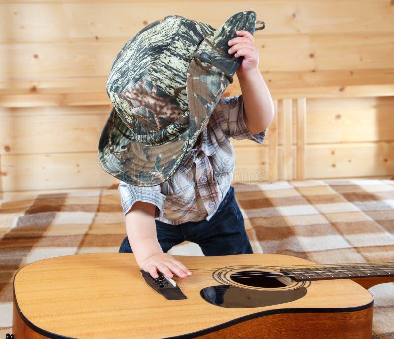 Pequeño bebé en el sombrero de vaquero que toca la guitarra acústica foto de archivo