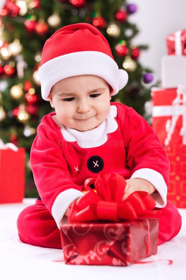 Pequeño bebé en los regalos abiertos del traje de Papá Noel para la Navidad imágenes de archivo libres de regalías