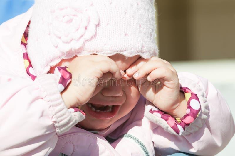 Pequeño bebé en ropa rosada que llora, retrato del primer foto de archivo libre de regalías