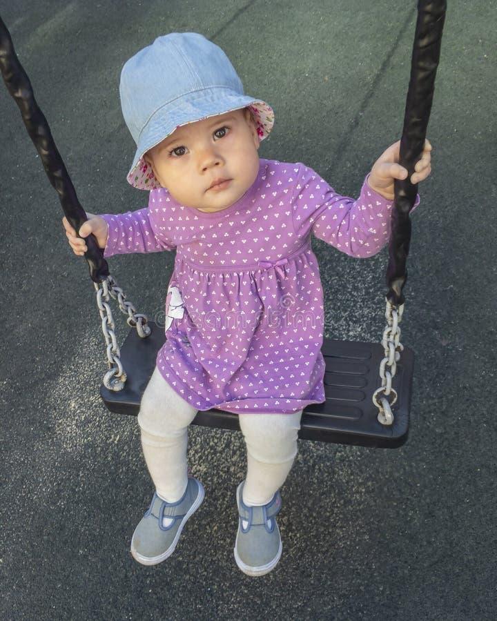 Pequeño bebé en un vestido púrpura que monta en un oscilación, un fondo oscuro, un retrato de un niño Chica joven seria linda que imágenes de archivo libres de regalías