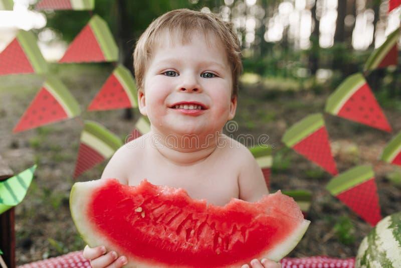 Pequeño bebé feliz que come la sandía al aire libre imágenes de archivo libres de regalías