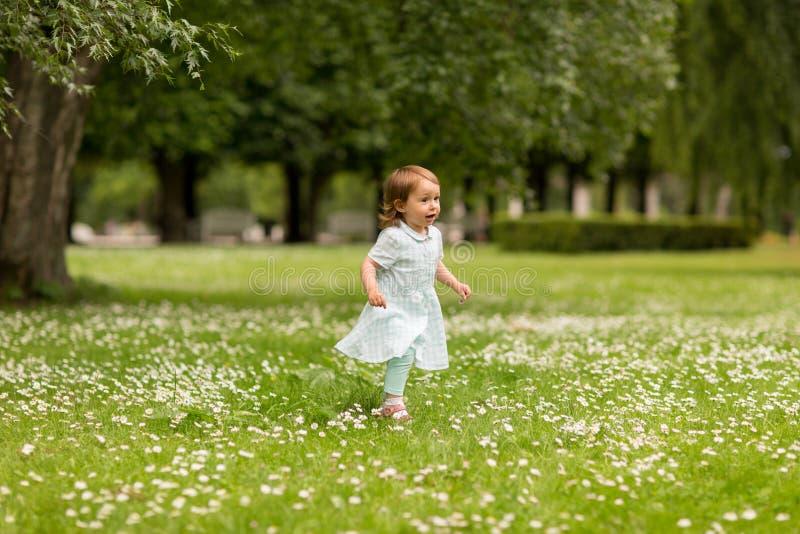 Pequeño bebé feliz que corre en el parque en verano fotografía de archivo