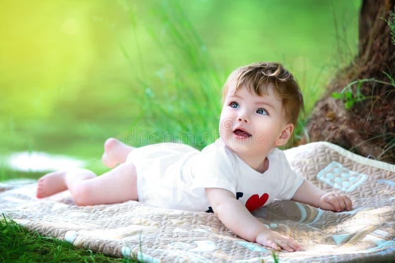 Pequeño bebé feliz que se divierte en el parque en el backg de la orilla del lago foto de archivo