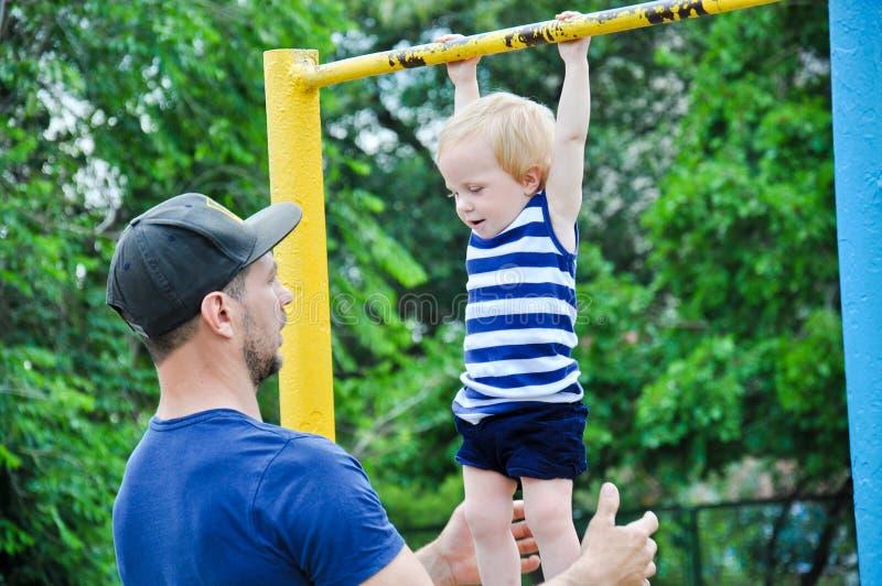 Pequeño bebé fuerte con su padre que juega deporte extremo fotos de archivo