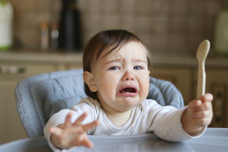 Pequeño bebé hambriento gritador con los rasgones en los ojos que se sientan en la silla de alta alimentación con la cuchara fotografía de archivo libre de regalías