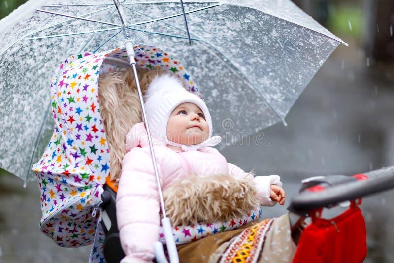 Pequeño bebé hermoso lindo que se sienta en el cochecito de niño o el cochecito en día frío con aguanieve, lluvia y nieve fotos de archivo