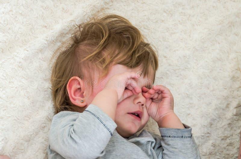 Pequeño bebé hermoso que miente en la cama, llorando y limpiando los rasgones de sus manos de los ojos foto de archivo