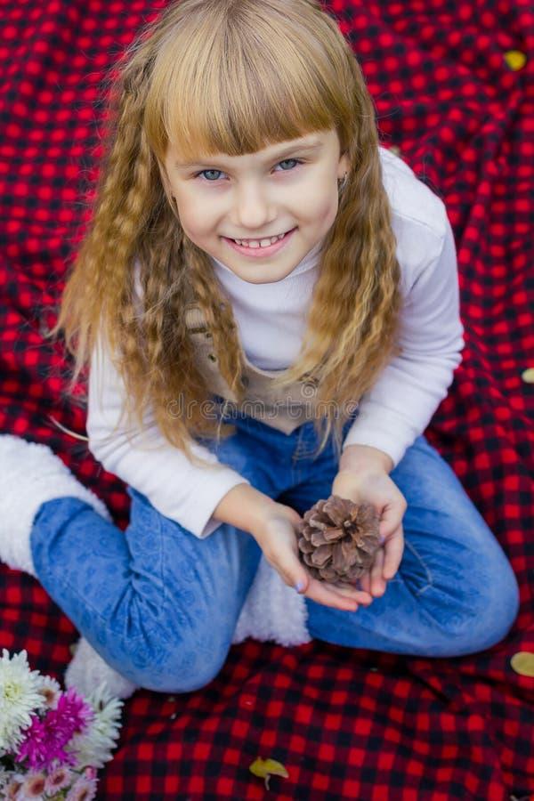 Pequeño bebé joven hermoso en un sombrero rosado con un terrón en sus manos Niño hermoso que se sienta en una tela escocesa roja imagen de archivo libre de regalías