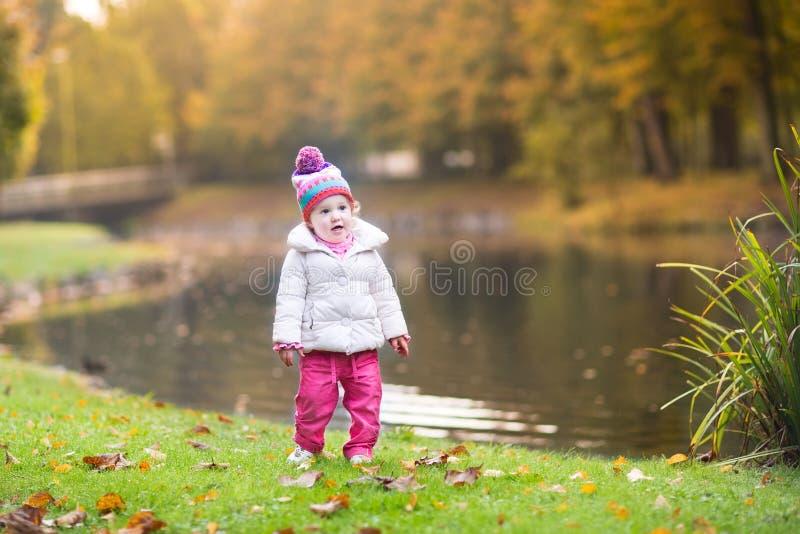 Pequeño bebé lindo al lado del río en parque del otoño imagenes de archivo
