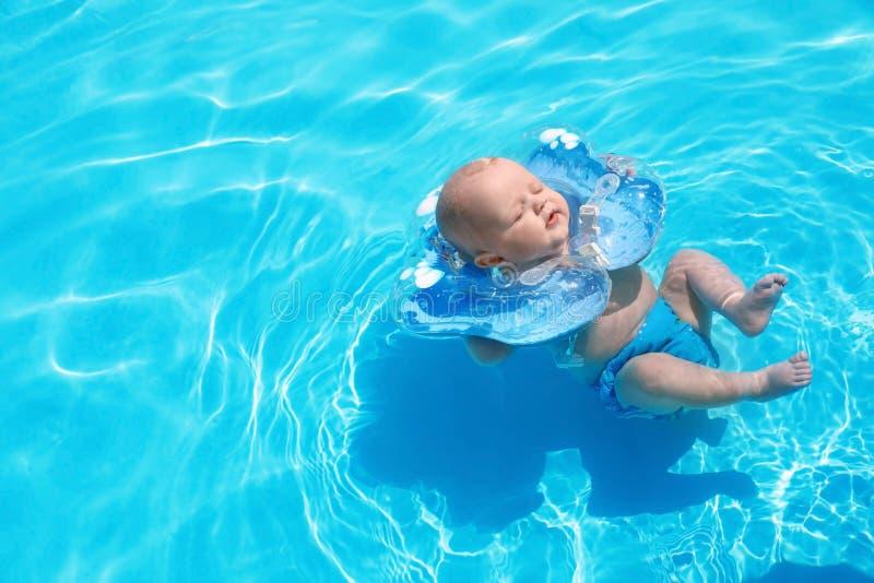 Pequeño bebé lindo con el anillo inflable del cuello en piscina imagenes de archivo