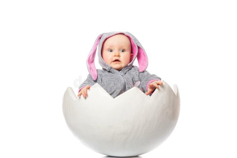 Pequeño bebé lindo con el traje del conejito en el huevo de Pascua En el fondo blanco Una sorpresa más buena foto de archivo