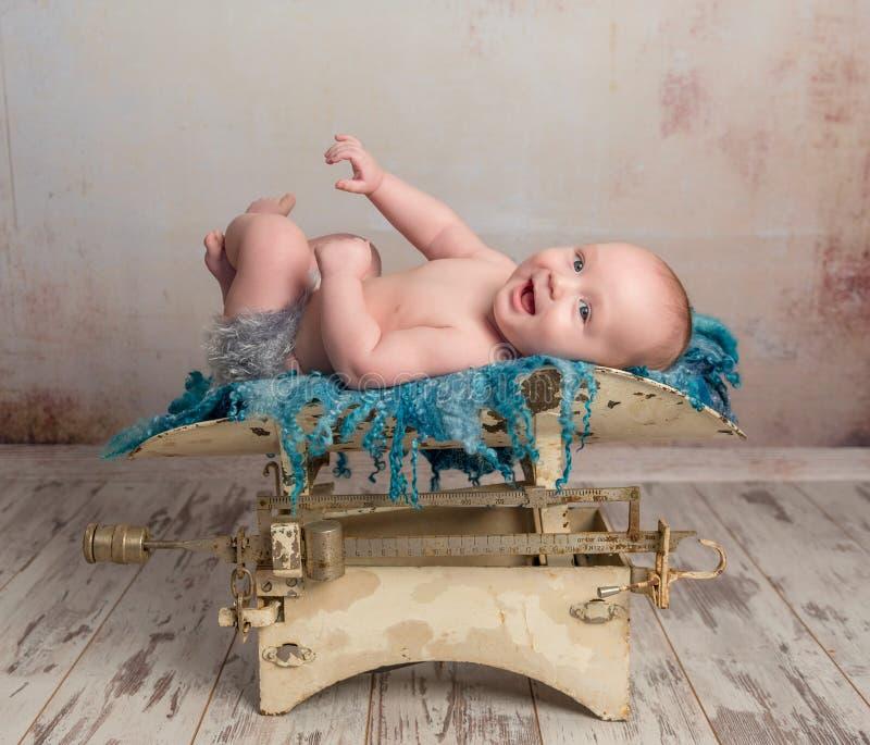 Pequeño bebé lindo con las piernas para arriba en escalas fotos de archivo