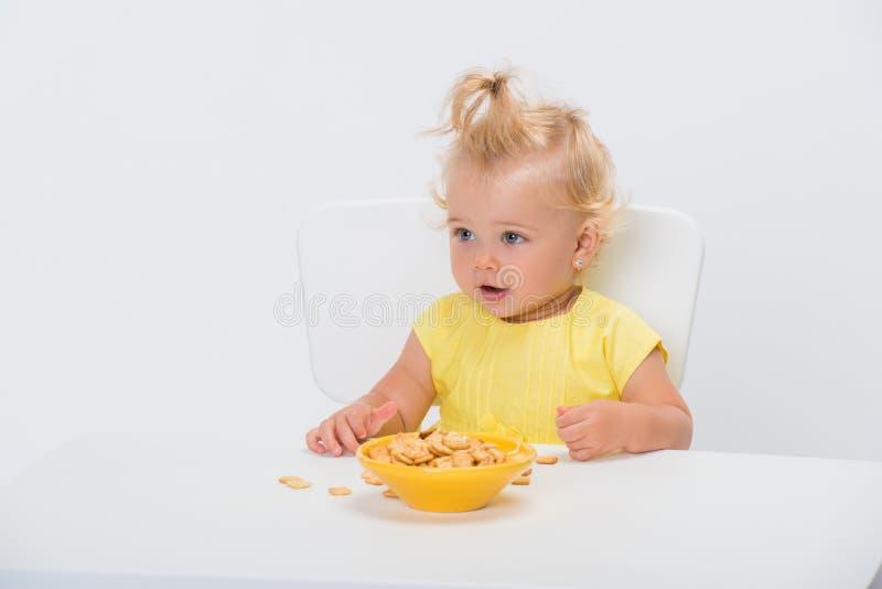 Pequeño bebé lindo de 1 año en la camiseta amarilla que come escamas del cereal en la tabla aislada en el fondo blanco fotos de archivo libres de regalías