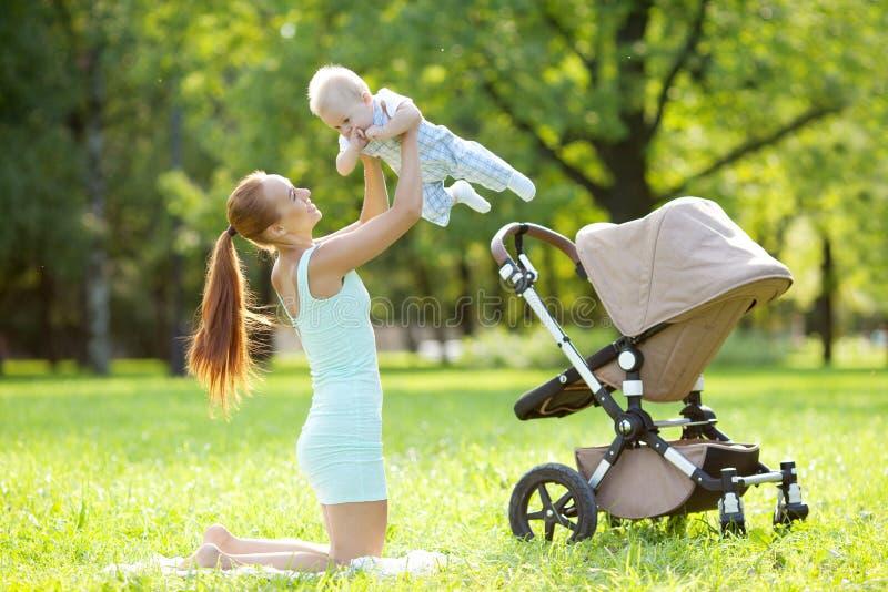 Pequeño bebé lindo en el parque con la madre en la hierba. Bab dulce fotos de archivo libres de regalías