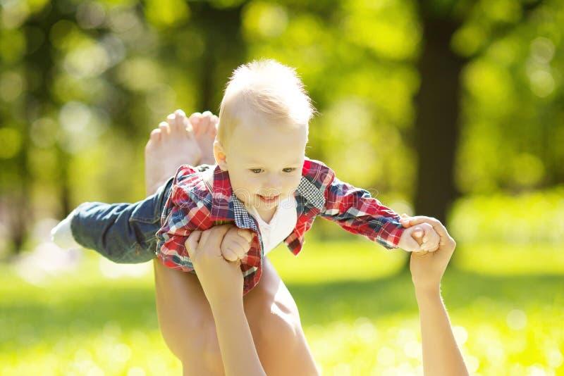 Pequeño bebé lindo en parque del verano con la madre en la hierba. Swee imagenes de archivo