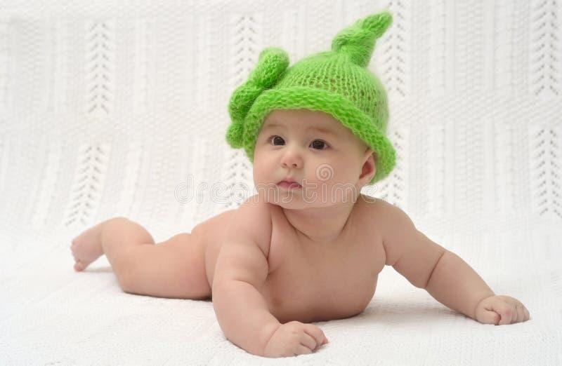 Pequeño bebé lindo en sombrero verde divertido fotografía de archivo