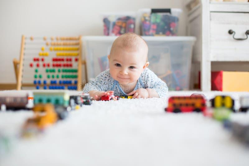 Pequeño bebé lindo, jugando con los coches del juguete en la alfombra en ji imagen de archivo
