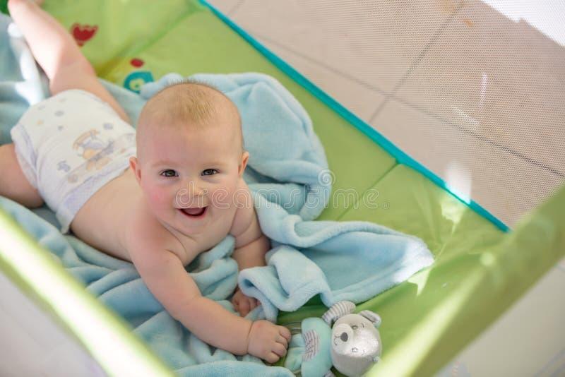 Pequeño bebé lindo, jugando con los juguetes en un pesebre móvil en un su fotos de archivo