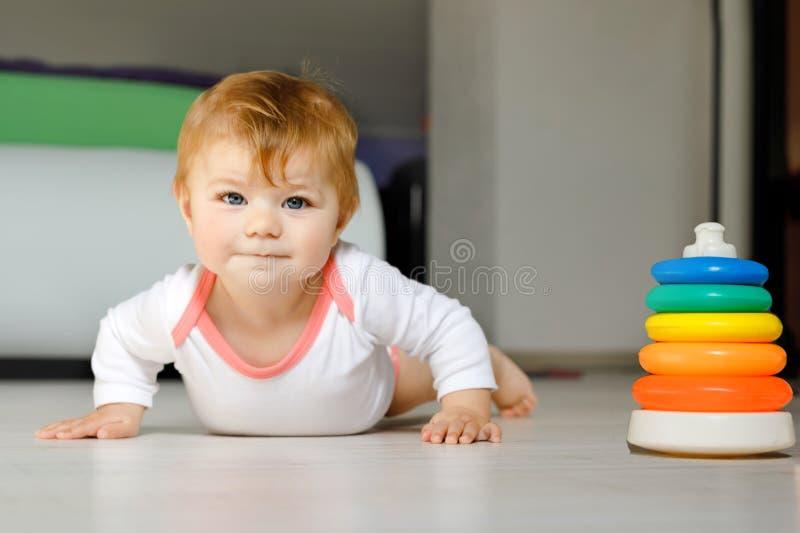 Pequeño bebé lindo que aprende arrastrarse Niño sano que se arrastra en sitio de los niños Niña pequeña sana feliz sonriente lind imágenes de archivo libres de regalías
