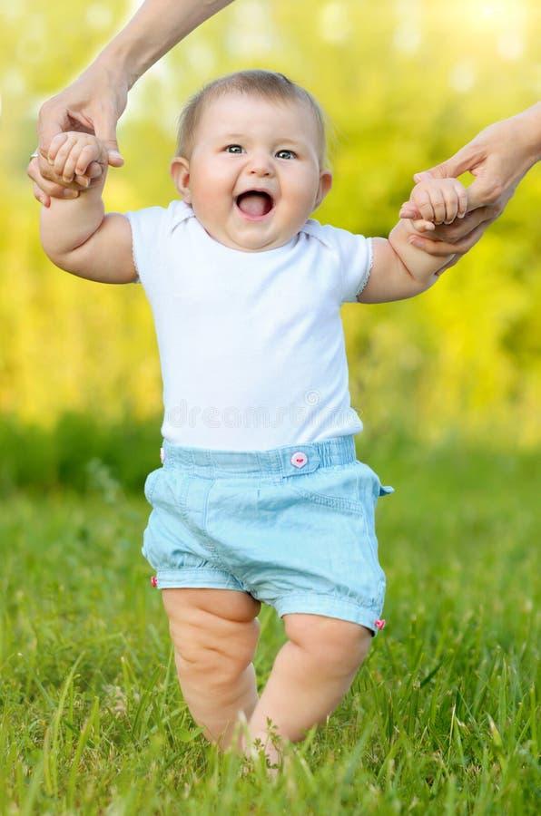 Pequeño bebé lindo que hace los primeros pasos foto de archivo libre de regalías