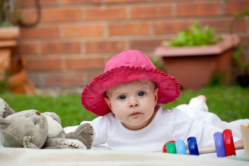 Pequeño bebé lindo que juega con sus juguetes imagenes de archivo
