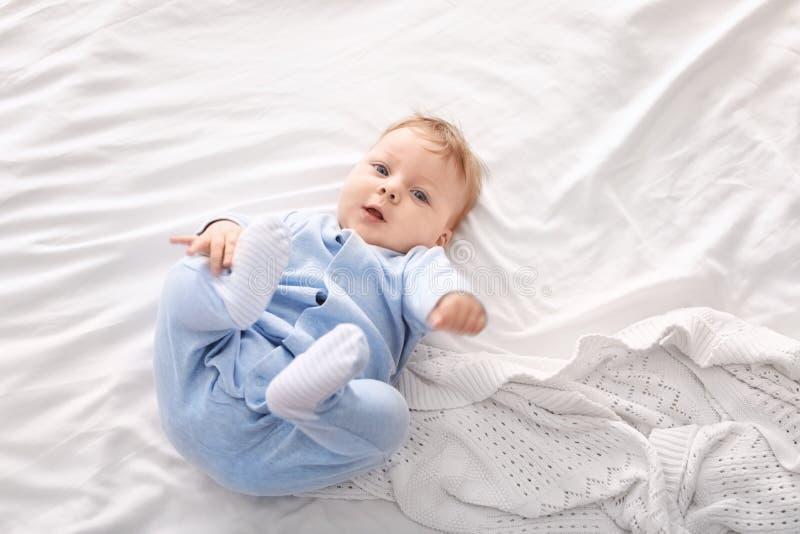 Pequeño bebé lindo que miente en cama, foto de archivo libre de regalías