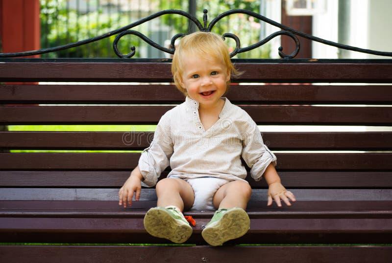 Pequeño bebé lindo que se sienta en banco fotografía de archivo