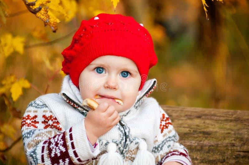 Pequeño bebé lindo que se sienta en el bosque y que come un panecillo foto de archivo