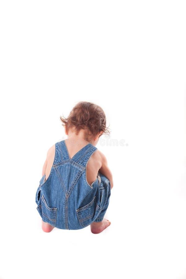 Pequeño bebé lindo que se sienta en fondo blanco aislado fotografía de archivo