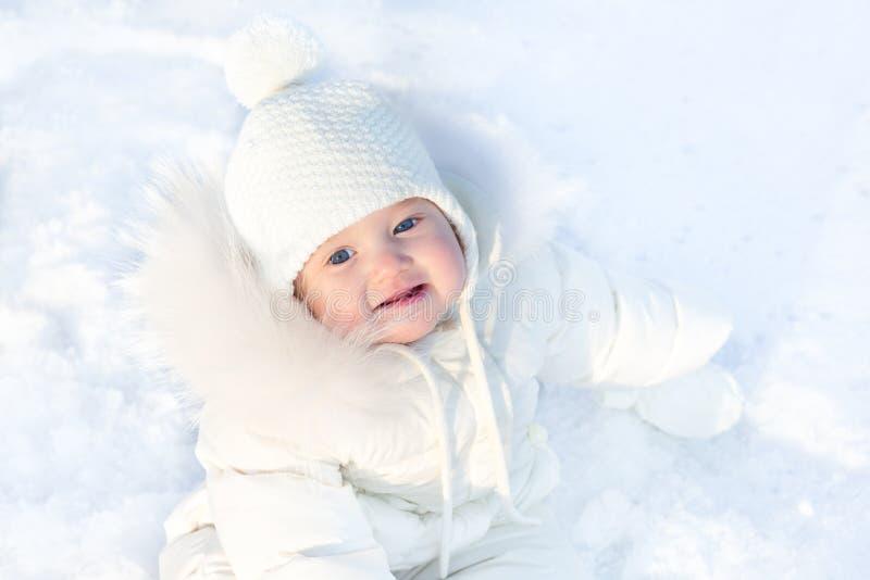 Pequeño bebé lindo que se sienta en nieve fresca del invierno imagen de archivo