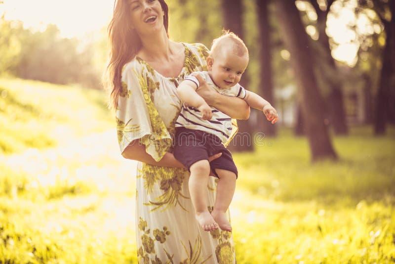 Pequeño bebé lindo y su madre en la naturaleza imagen de archivo libre de regalías