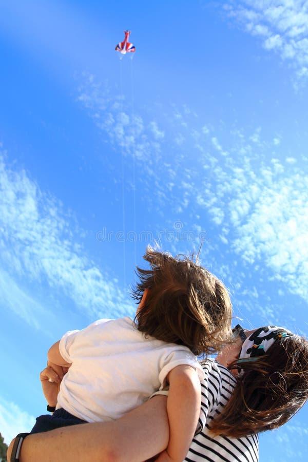 Pequeño bebé lindo y su momia que miran fijamente una cometa que vuela arriba en el cielo de una playa en Costa Brava, Girona, Ca imagen de archivo libre de regalías