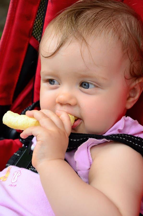 Pequeño bebé que come el bocado del soplo del maíz imagen de archivo