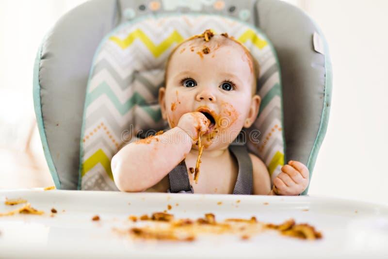 Pequeño bebé que come su cena y que hace un lío fotografía de archivo